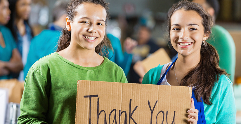 Two girls holding thank you sign