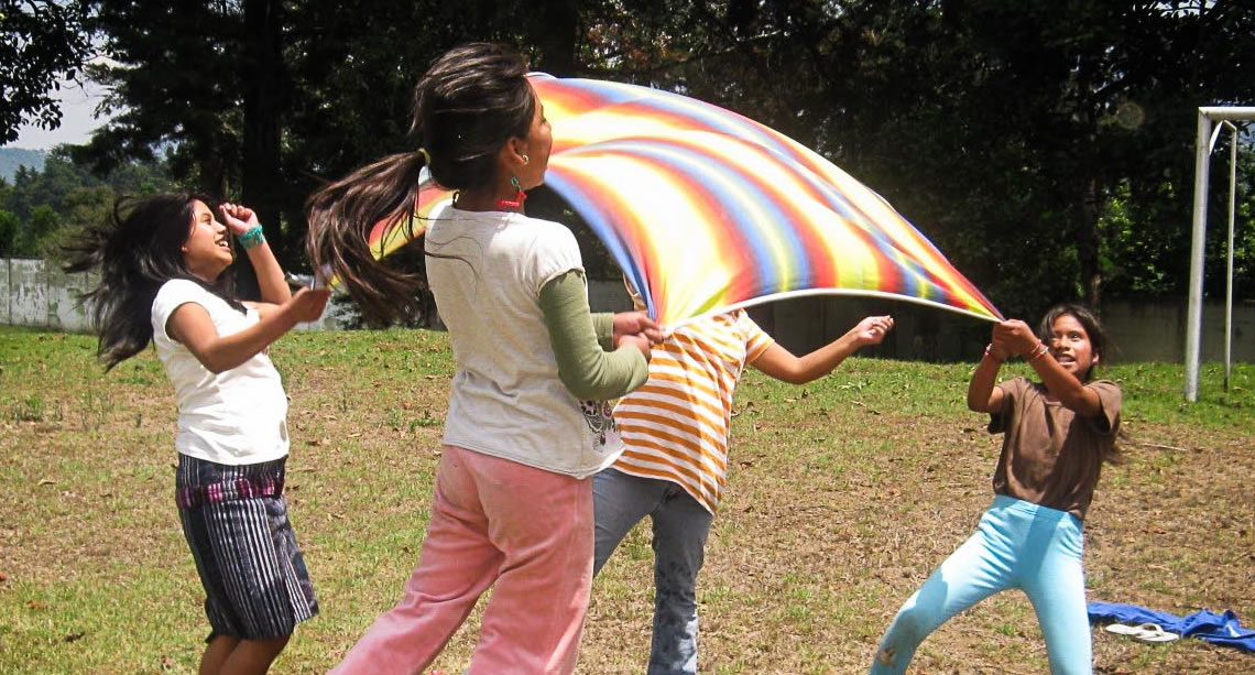 Kids playing with parachute outside