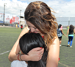 Woman Hugging Youth on Soccer Field